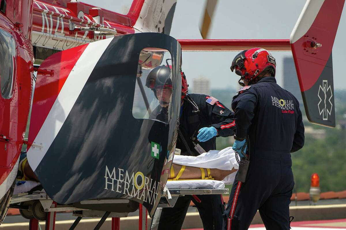A Life Flight crew in 2012 unloads a trauma patient from the helicopter on the helipad at Memorial Hermann.
