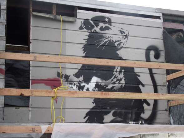 In December 2010, workers from Brothers Collins Woodworking prepare to remove a painting of a rat clutching a magic marker by the anonymous street artist Banksy, who left the graffiti earlier in 2010 on the side of the Red Victorian inn at 1665 Haight St. in San Francisco. Art enthusiast Brian Greif is now seeking to restore and publicly display the piece.