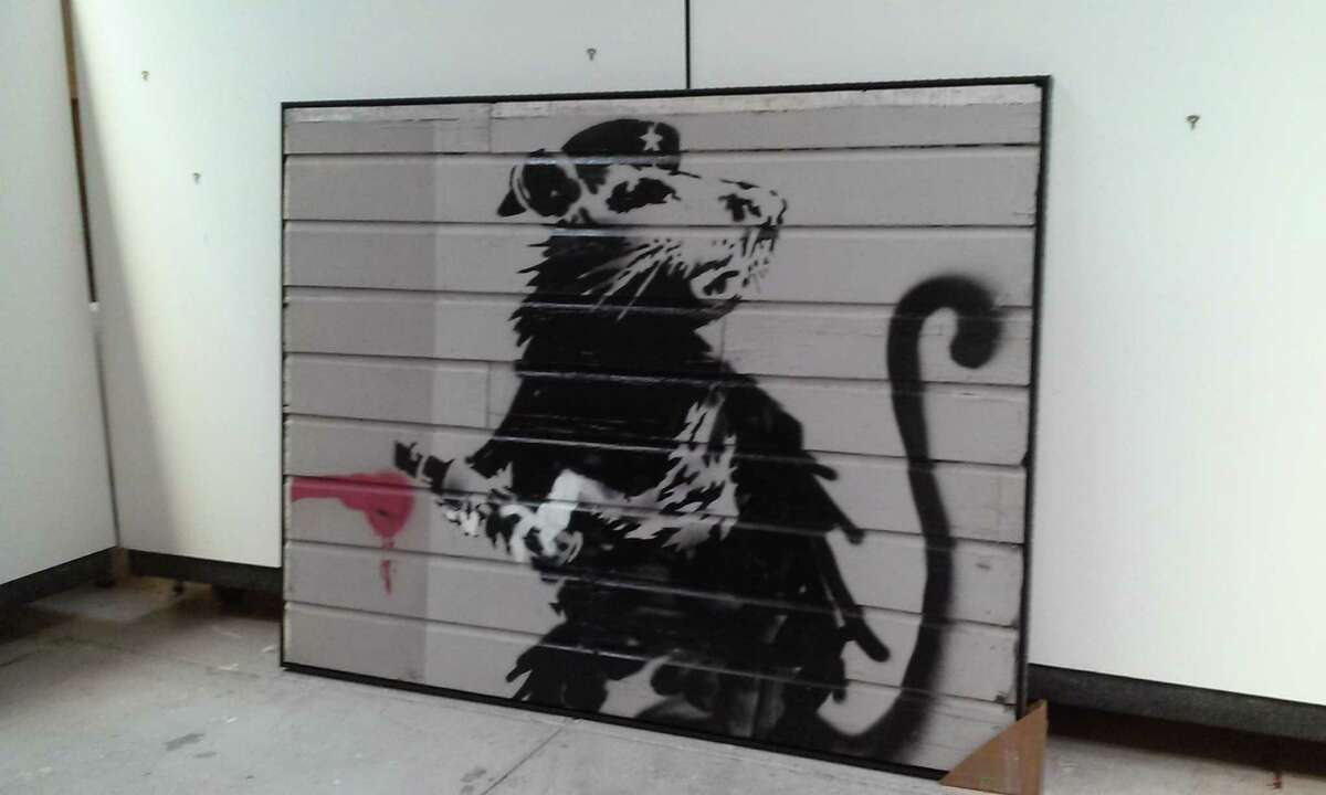 A newly restored work by British graffiti artist Banksy is on display at the U.S. Bank Tower in Los Angeles after it was saved from the side of the Red Victorian in San Francisco.