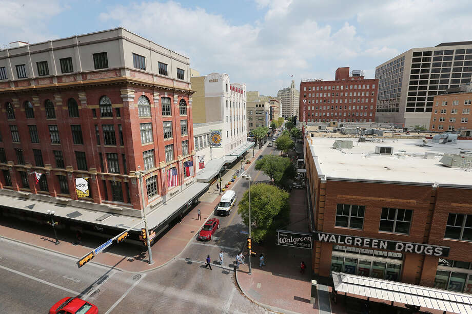 Pedestrians walk across Houston Street by buildings owned by Federal Realty. Thursday, Oct. 2, 2014. Among the buildings own by the Maryland-based company are the Vogue building, left, the Kress building, center and the Walgreens building. The company is planning on selling all of its Houston Street properties. Photo: JERRY LARA, San Antonio Express-News / © 2014 San Antonio Express-News