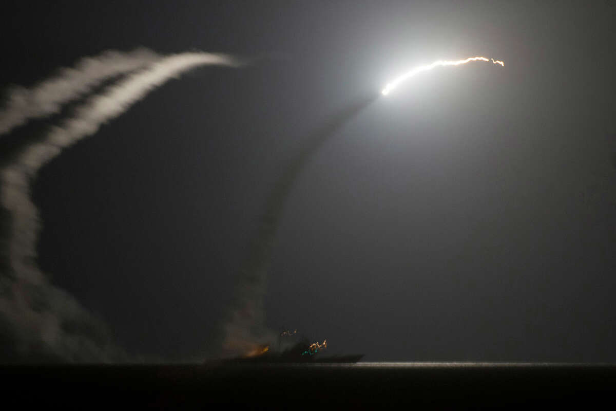 In this photo released by the U.S. Navy, the guided-missile cruiser USS Philippine Sea launches a Tomahawk cruise missile at Islamic State group positions in Syria as seen from the aircraft carrier USS George H.W. Bush in the Arabian Gulf on Tuesday, Sept. 23, 2014. Syria said Tuesday that Washington informed President Bashar Assad's government of imminent U.S. airstrikes against the Islamic State group, hours before an American-led military coalition pounded the extremists' strongholds across northern and eastern Syria.(AP Photo/Eric Garst, U.S. Navy)