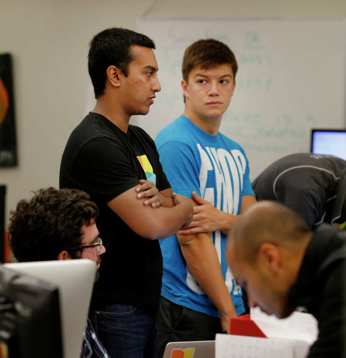 Pablo Lleras (right) listens as Pixlee co-founder Awad Sayeed talks during a meeting. Pixlee uses a note-taking platform from Do, which has received funding from Salesforce.com.