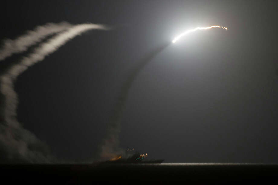 In this photo released by the U.S. Navy, the guided-missile cruiser USS Philippine Sea launches a Tomahawk cruise missile at Islamic State group positions in Syria as seen from the aircraft carrier USS George H.W. Bush in the Arabian Gulf on Tuesday, Sept. 23, 2014. Syria said Tuesday that Washington informed President Bashar Assad's government of imminent U.S. airstrikes against the Islamic State group, hours before an American-led military coalition pounded the extremists' strongholds across northern and eastern Syria.(AP Photo/Eric Garst, U.S. Navy) Photo: MC1 Eric Garst, Associated Press / AP2014