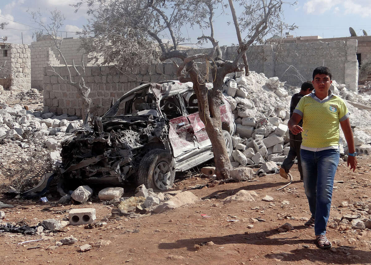 A Syrian youth walks past the wreckage of a vehicle following the U.S.-led coalition's airstrikes against the Islamic State of Iraq and the Levant (ISIL) on a residential area in Idlib, Syria on September 23, 2014.