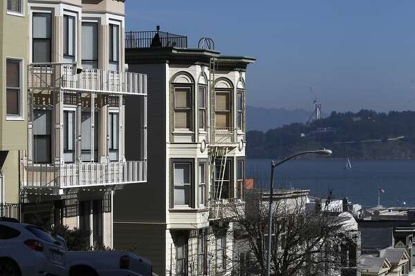 An apartment building (left) owned by Peter Yu and Ada Chu is seen on Vallejo Street in San Francisco, Calif. on Tuesday, Feb. 12, 2013. City Attorney Dennis Herrera has ordered the couple to pay $525,000 in back wages to several employees of their restaurant after forcing them to work long hours at below minimum wage. They also forced some to work as maids at their home.