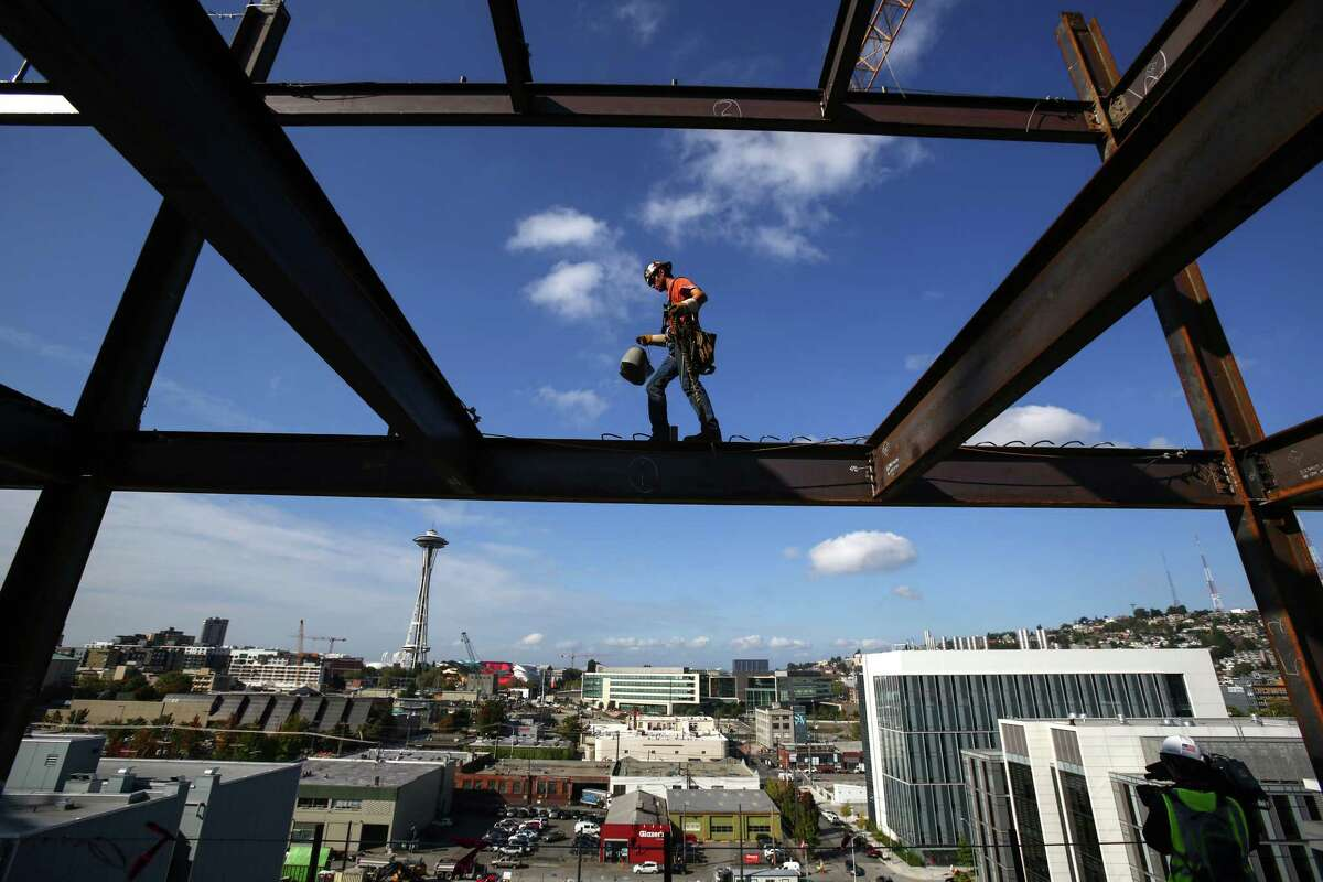 Iron worker Jake Lucas balances as he negotiates a beam on the 11th floor of Vulcan's Block 45 Project in South Lake Union. The building is being assembled faster than most as two tower cranes are being used on the project. When finished the building will be 12 stories tall and almost 500,000 total square feet. Photographed on Thursday, October 2, 2014.