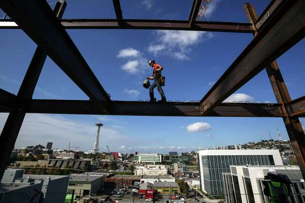 Iron worker Jake Lucas balances as he negotiates a beam on the 11th floor of Vulcan's Block 45 Project in South Lake Union. The building is being assembled faster than most as two tower cranes are being used on the project. When finished the building will be 12 stories tall and almost 500,000 square feet. Photographed on Thursday, October 2, 2014.