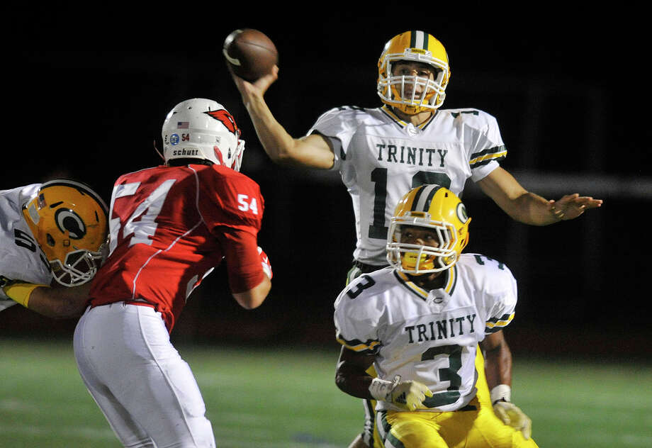 Trinity Catholic quarterback Anthony Lombardi releases the ball while under pressure from Greenwich's Taulant Bici during their football game at Greenwich High School in Greenwich, Conn., on Thursday, Oct. 2, 2014. Greenwich won, 28-13. Photo: Jason Rearick / Stamford Advocate