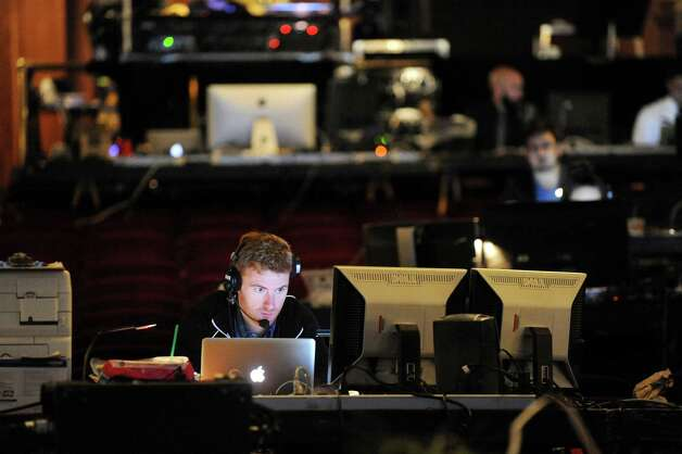 "Assistant lighting designer Wilburn Bonnell, center, works on the production of ""Newsies"" from a makeshift desk in the seating area on Wednesday, Oct. 1, 2014, at Proctors Theatre in Schenectady, N.Y. (Cindy Schultz / Times Union) Photo: Cindy Schultz / 00028846A"