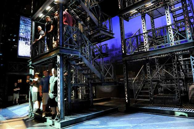 "Workers add their body weight to one of the towers as it gets moved around on the set of ""Newsies"" on Wednesday, Oct. 1, 2014, at Proctors Theatre in Schenectady, N.Y. There are three towers on the set at 4,500 pounds each. (Cindy Schultz / Times Union) Photo: Cindy Schultz / 00028846A"