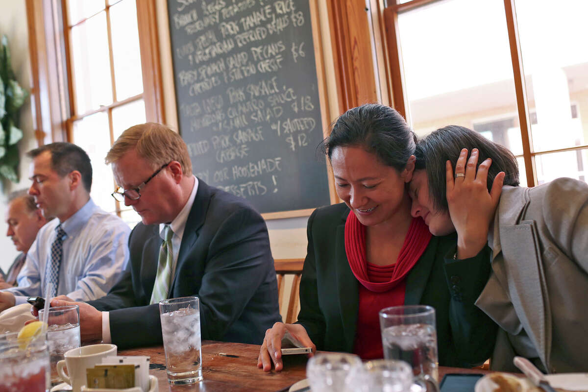 Nicole Dimetman, right, relaxes with her wife, Cleo DeLeon, as they have lunch with fellow plaintiffs Mark Phariss and his partner, Victor Holmes, far left, as they have lunch with their legal team at Liberty Bar after the hearing for their request for a preliminary injunction to declare Texas' ban on same-sex marriage unconstitutional at the John H. Wood, Jr. U.S. Courthouse in San Antonio on Wednesday, Feb. 12, 2014.