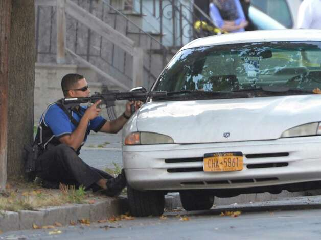 An Albany police officer takes aim at a house that was alleged to have the shooter hiding inside Thursday afternoon, Oct. 2, 2014, in Albany, N.Y. The shooter was not found in the house after the Emergency Response Team searched the house at 527 Clinton Avenue.  (Skip Dickstein/Times Union) Photo: SKIP DICKSTEIN