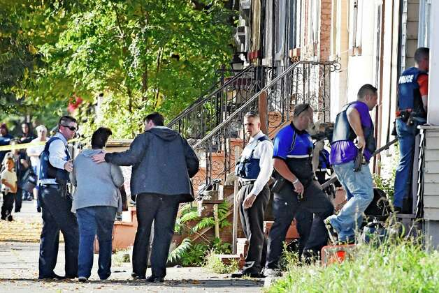 A woman is escorted out as Albany Police Emergency Response Team enter 527 Clinton Avenue after is was alleged that a shooting suspect took cover inside Thursday afternoon, Oct. 2, 2014, in Albany, N.Y. (Skip Dickstein/Times Union) Photo: SKIP DICKSTEIN