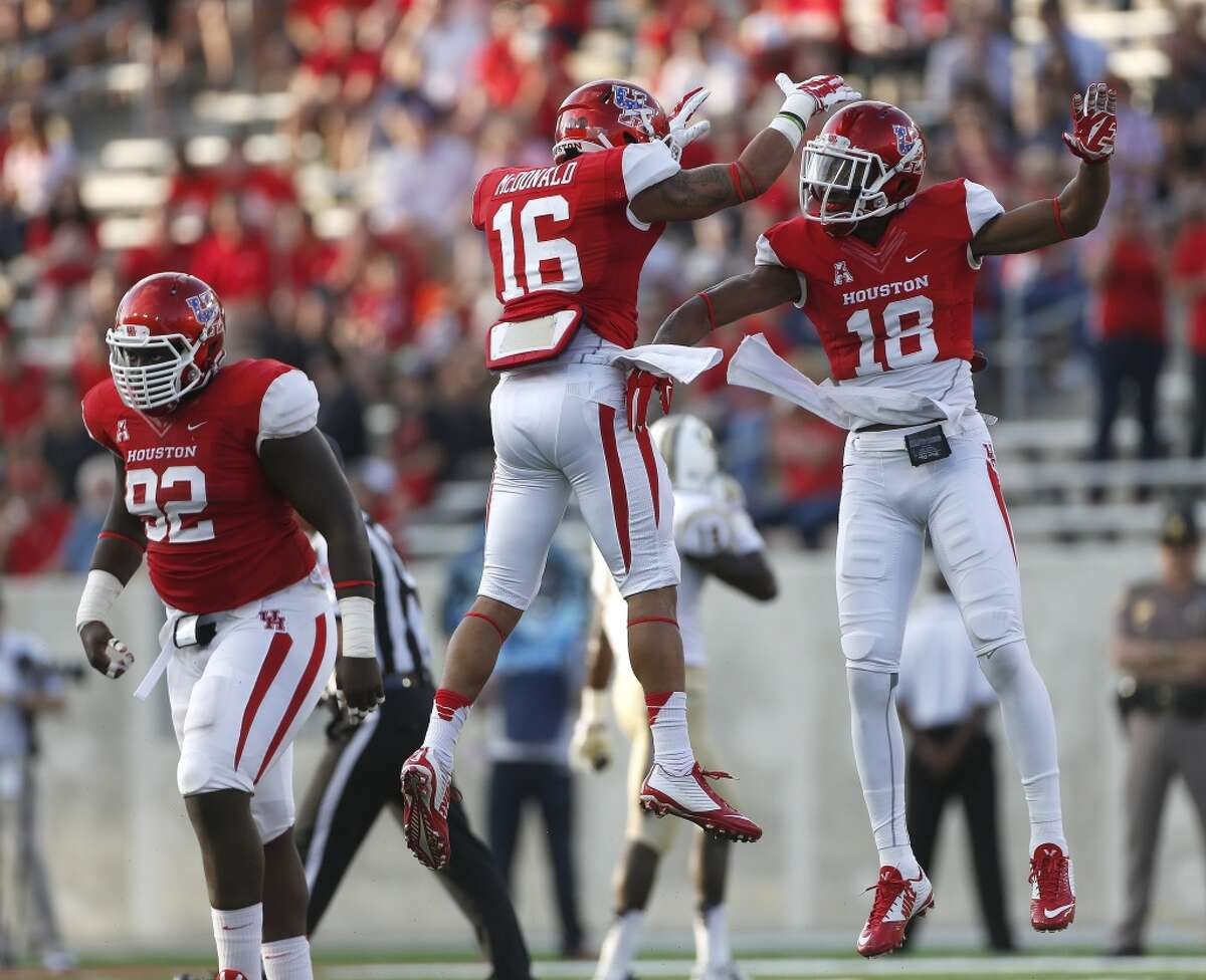 Houston Cougars defensive backs Adrian McDonald (16) and Lee Hightower (18) celebrate stopping UCF Knights offense during the first half of a college football game at TDECU Stadium at the University of Houston, Thursday, Oct. 2, 2014, in Houston. ( Karen Warren / Houston Chronicle )