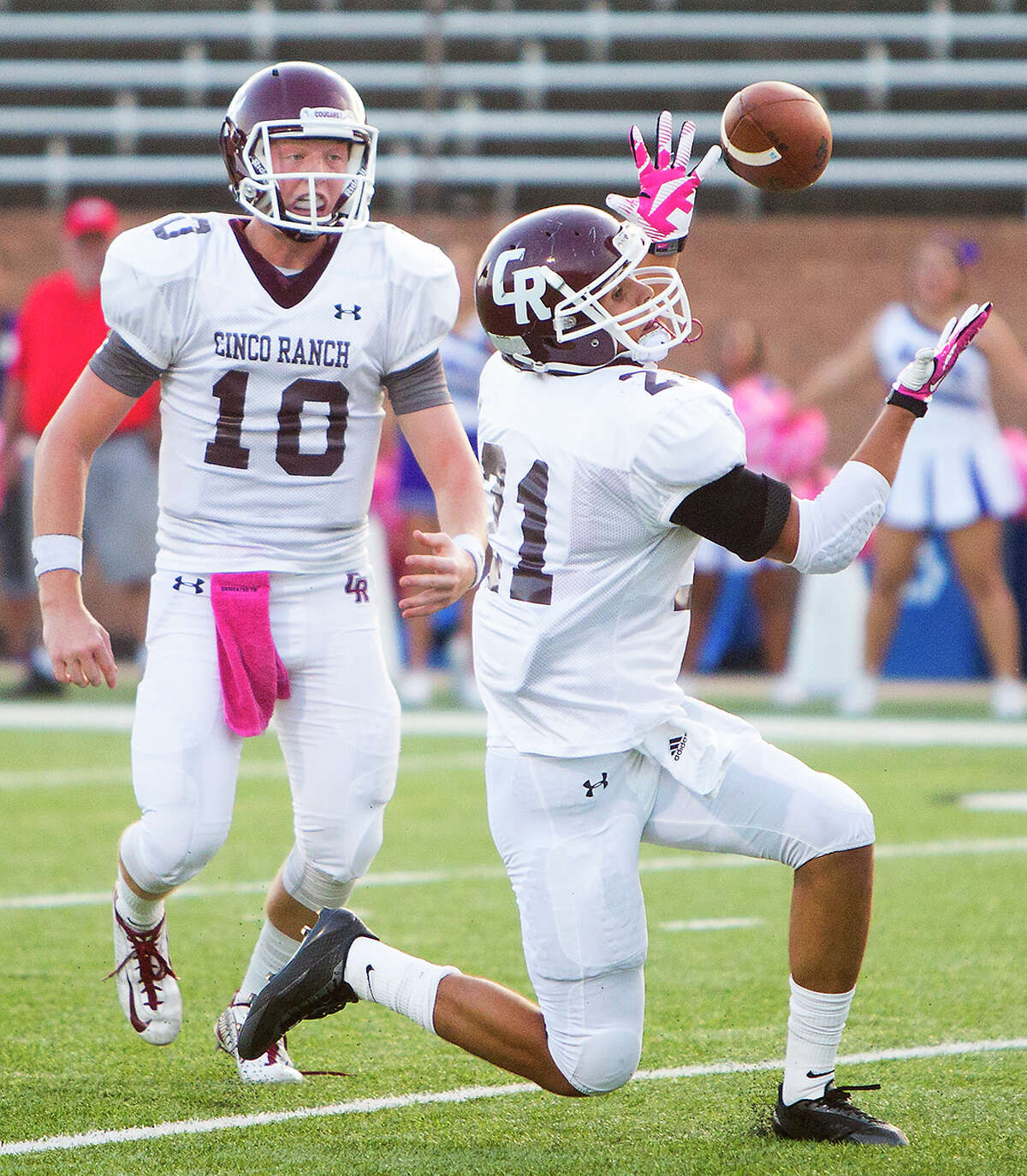 Cinco Ranch running back Jonathan Lugo bobbles a pass from quarterback Russell Morrison, left, during the first half of a football game against Morton Ranch High School at Rhodes Stadium, Thursday, Oct. 2, 2014, in Katy.