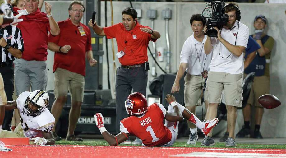 UH quarterback Greg Ward Jr. winds up without the football on his dive into the end zone in the waning seconds of Thursday night's game at TDECU Stadium. Central Florida's Brandon Alexander, left, knocked the ball loose for a touchback. Photo: Karen Warren, Staff / © 2014 Houston Chronicle