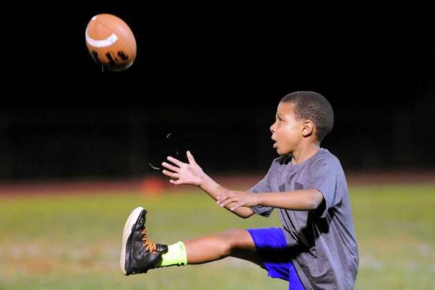 Water boy Andre Deumaga, 8, nephew of Shaker's head coach Greg Sheeler, plays with a football during halftime in their game against La Salle on Thursday, Oct. 2, 2014, at Shaker High in Latham, N.Y. (Cindy Schultz / Times Union) Photo: Cindy Schultz / 00028778A
