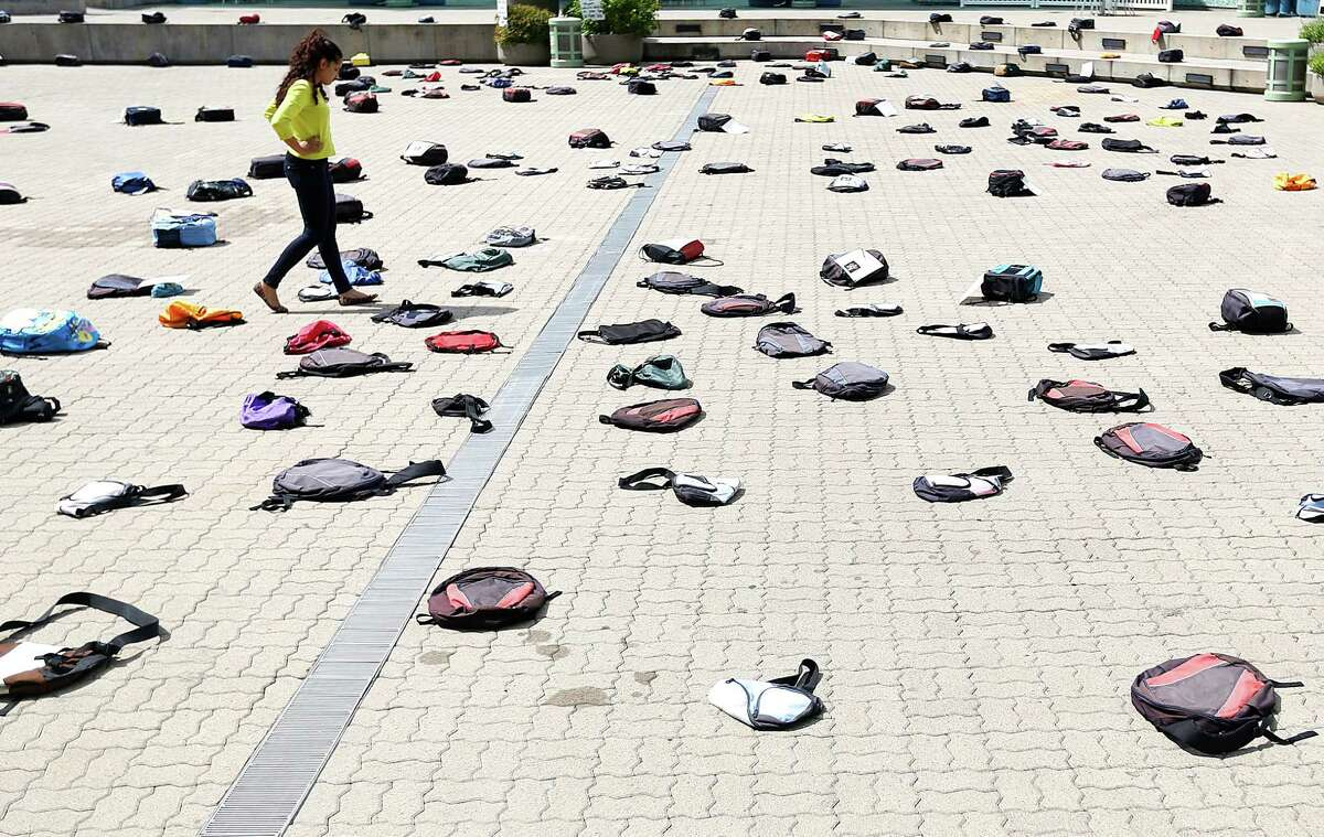 """After spotting bags coving the ground of Jones Plaza, Alanna Murray walked over to see the 1,100 backpacks, many with personal stories, representing the estimated 1,100 college students who die by suicide each year at Thursday, Oct. 2, 2014, in Houston. """"It's very sad and overwhelming,"""" Murray said. """"Seeing all these bags is like a symbol for whats going on."""""""