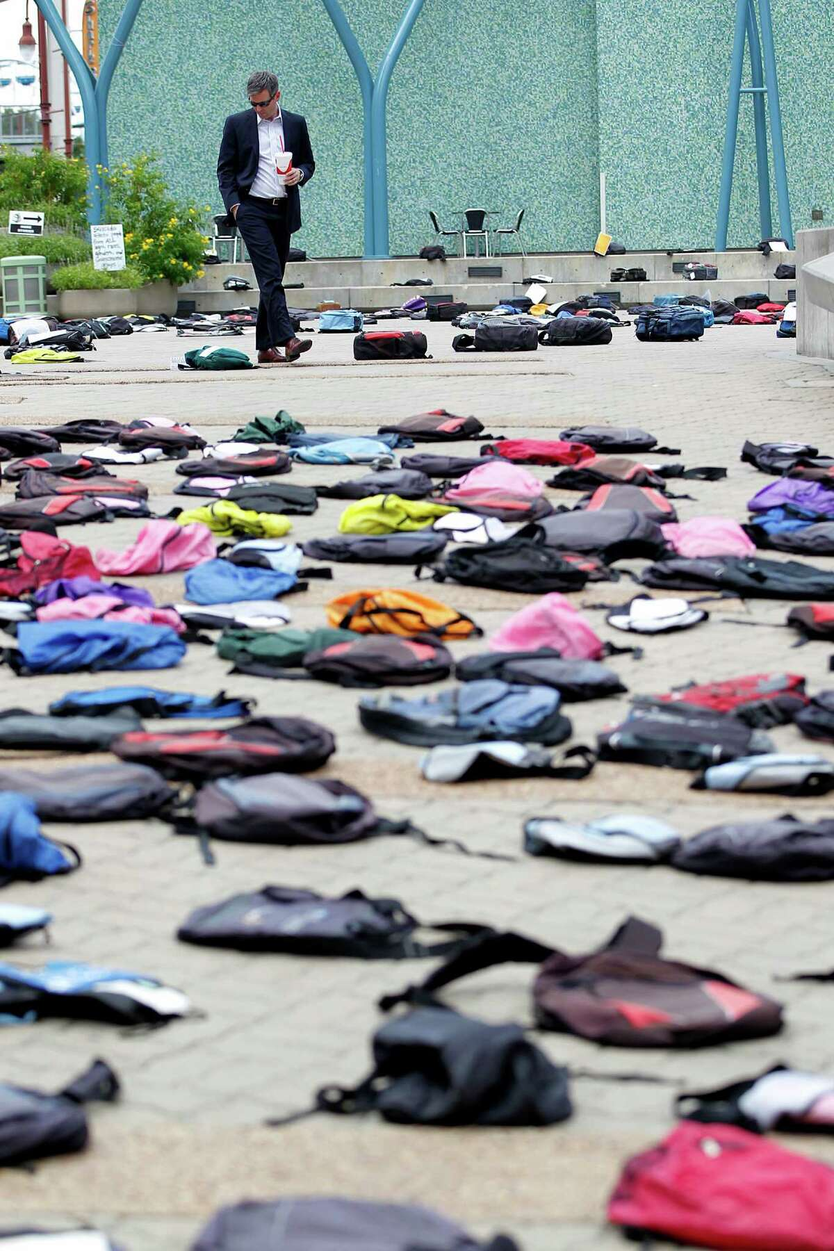 """Michael Norvell looks at the one of the 1,100 backpacks, many with personal stories, representing the estimated 1,100 college students who die by suicide each year at Jones Plaza Thursday, Oct. 2, 2014, in Houston. """"It's powerful,"""" Norvell said. The organization Send Silence Packing, a program of Active Minds, Inc., stopped in Houston for the day with their touring exhibit to brings awareness to students with mental health disorders. Suicide is the second leading cause of death for people ages 15-24 as stated by the organization Suicide Awareness Voices of Education."""