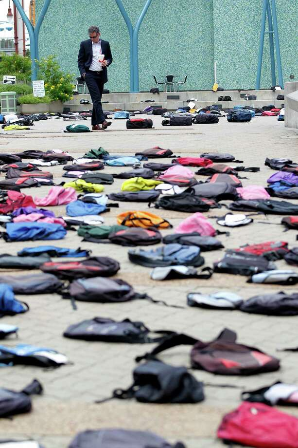 "Michael Norvell looks at the one of the 1,100 backpacks, many with personal stories, representing the estimated 1,100 college students who die by suicide each year at Jones Plaza Thursday, Oct. 2, 2014, in Houston.  ""It's powerful,"" Norvell said. The organization Send Silence Packing, a program of Active Minds, Inc., stopped in Houston for the day with their touring exhibit to brings awareness to students with mental health disorders. Suicide is the second leading cause of death for  people ages 15-24 as stated by the organization Suicide Awareness Voices of Education. Photo: Johnny Hanson, Houston Chronicle / © 2014  Houston Chronicle"