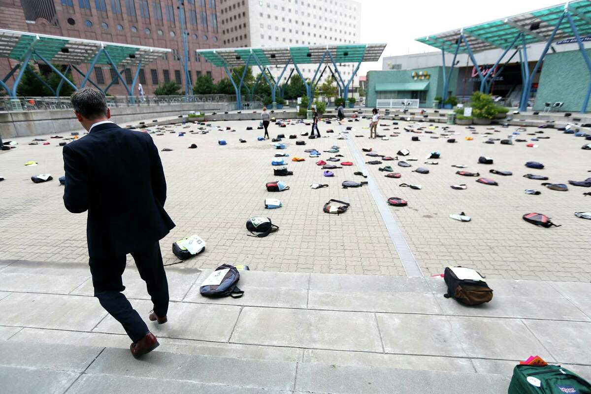 Michael Norvell looks at the one of the 1,100 backpacks, many with personal stories, representing the estimated 1,100 college students who die by suicide each year at Jones Plaza Thursday, Oct. 2, 2014, in Houston.