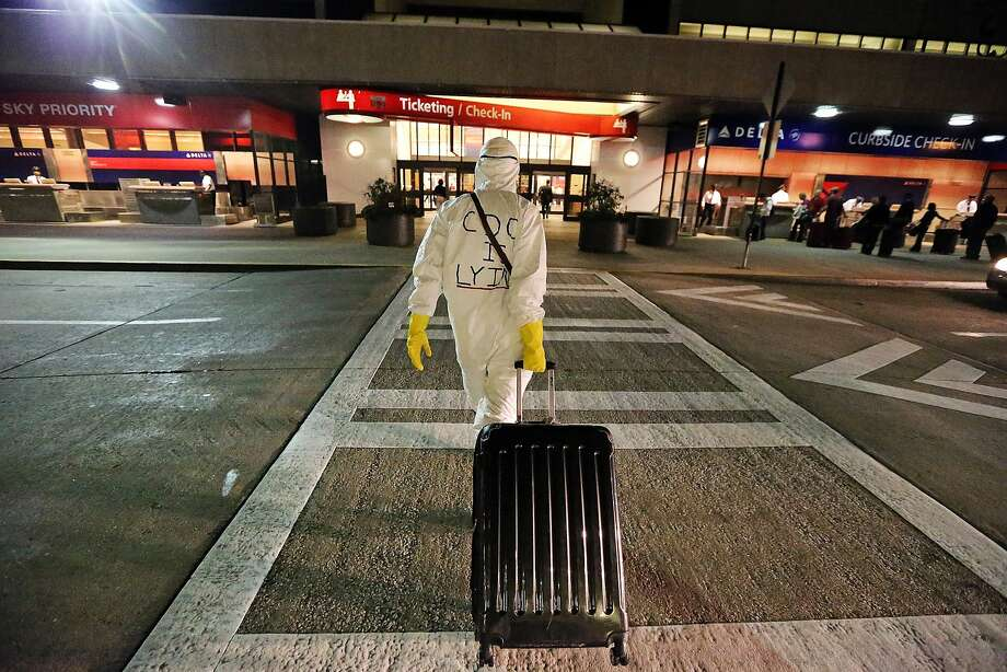 Two days after a man in Texas was diagnosed with Ebola, Dr. Gil Mobley, a Missouri doctor, walks to Hartsfield-Jackson Atlanta International Airport to check in and board a plane dressed in full protection gear Thursday morning, Oct. 2, 2014, in Atlantat. He was protesting what he called mismanagement of the crisis by the federal Centers for Disease Control and Prevention. (AP Photo/Atlanta Journal-Constitution, John Spink) Photo: John Spink, Associated Press