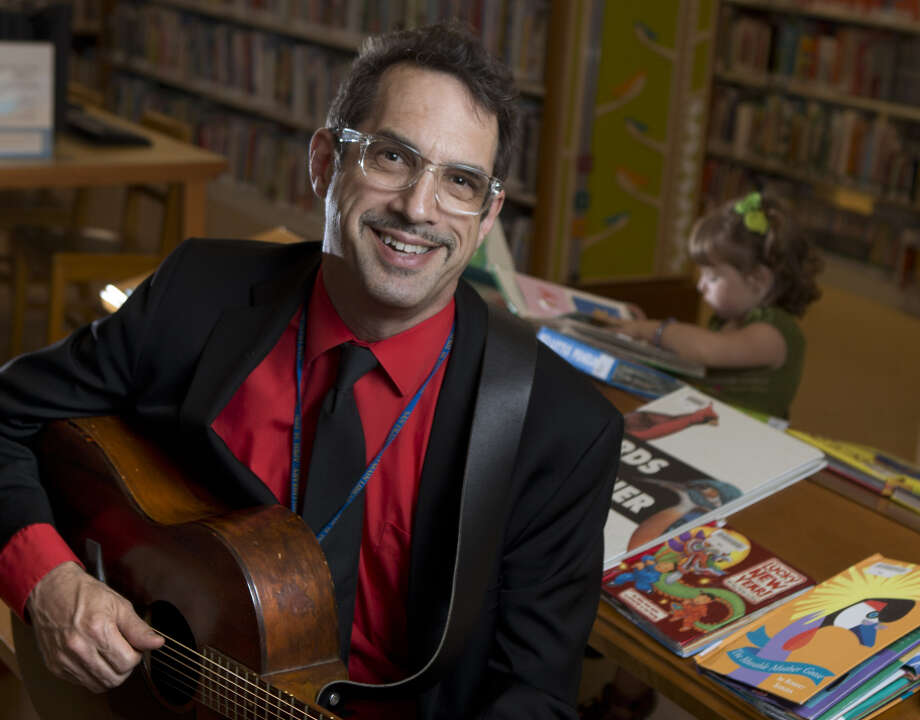 Benjamin Cohen, acting branch manager and children's librarian for the San Francisco Public Library Park Branch with Eloise Egan, 3, reading books behind him. Photo: Carlos Avila Gonzalez / The Chronicle / ONLINE_YES
