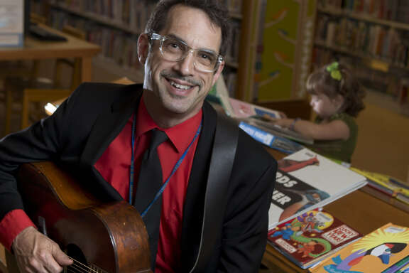 Benjamin Cohen, acting branch manager and children's librarian for the San Francisco Public Library Park Branch with Eloise Egan, 3, reading books behind him.