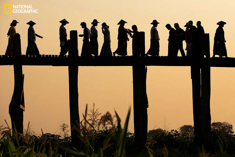 Ladies with Conical hats going to the right while locals, Monks, Kids, tourist going to the left as they were walking on the U Bien Bridge made out of teakwood at Mandalay, Myanmar. Photo: April Badilles, April Badilles, National Geographic 2014 Photo Contest U Bien Bridge Crossing