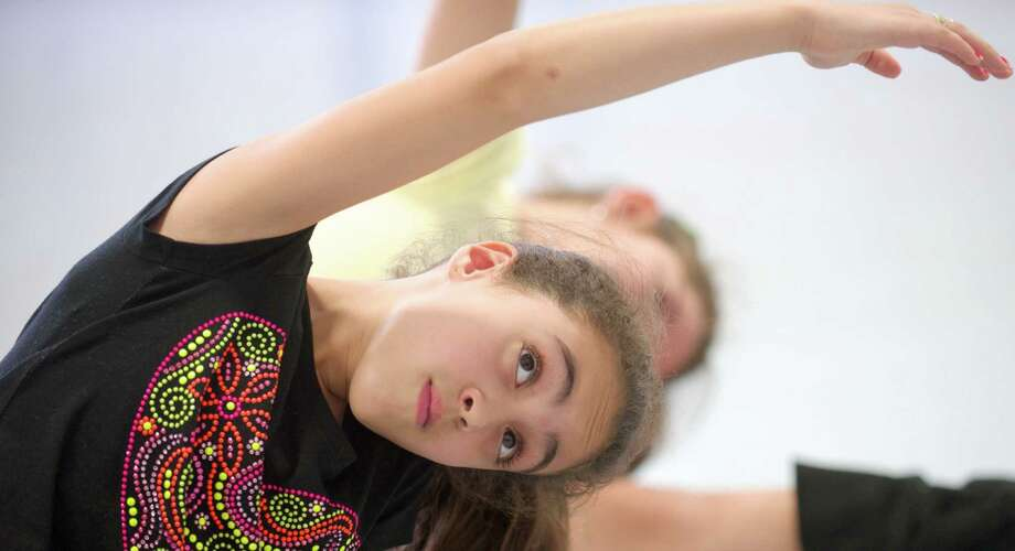 Jennifer Demouraes, 9, of Danbury, stretches during an after-school dance program at Shelter Rock Elementary School, in Danbury. The Connecticut Ballet has an after-school dance program at three Danbury , Conn, schools, including Shelter Rock. The program is hosted by the school systems Extra Learning Program and was made possible with help from a grant from Connecticut's Office of the Arts. On Thursday, October 2, 2014, the students were learning Brazilian dance moves with Connecticut Ballet teaching artist Thelma Ladeira. Photo: H John Voorhees III / The News-Times Staff Photographer