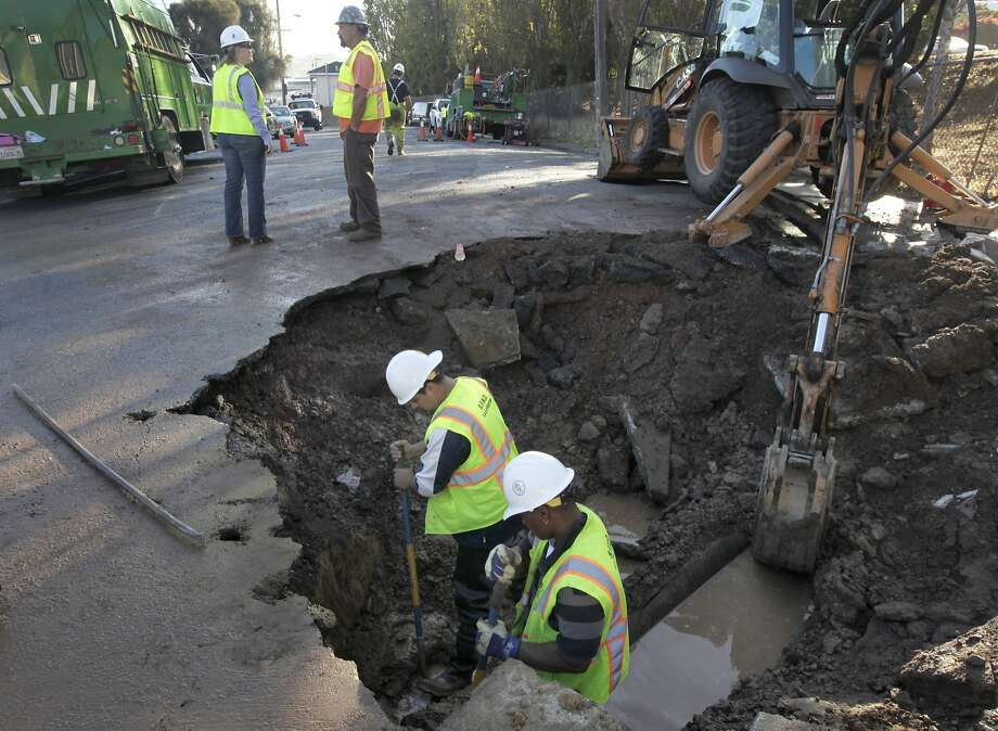 A water department crew repairs an underground water main which burst shortly after midnight, sending millions of gallons of water rushing down Keith Avenue in San Francisco, Calif. on Friday, Oct. 3, 2014. Officials hope to restore water service by afternoon. Photo: Paul Chinn, The Chronicle