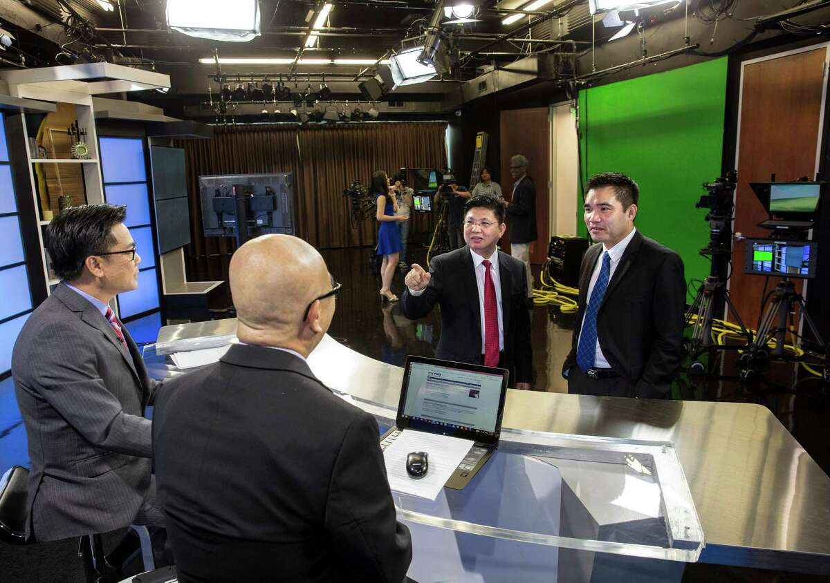 VIETV newscasters Quang Chuong, left, and Co Pham talk with the president of the company, Robert Pham, and founder Kevin Ngo in the TV station's studio.