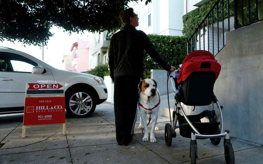 Andrew Sinyaver and dog, Max, stand outside an open house on 23rd Avenue in S.F. The three-bedroom house, with a one-bedroom cottage, is listed at $2.2 million. Photo: Scott Strazzante / The Chronicle / ONLINE_YES