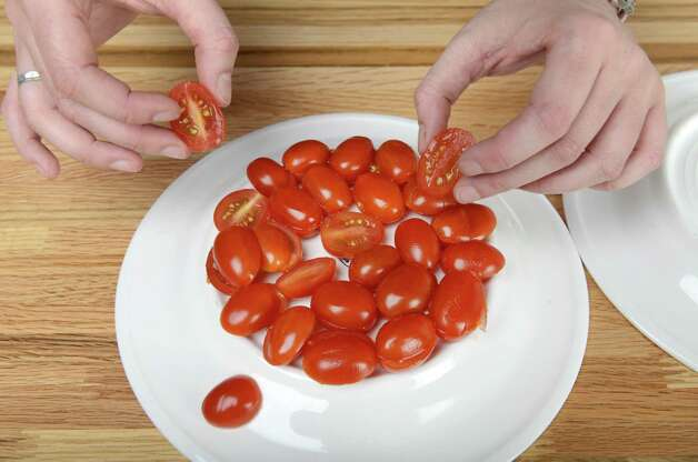 Cherry tomatoes held in place for cutting by sandwiching them between two plates Wednesday, Aug. 20, 2014, at the Times Union in Colonie, N.Y. (Will Waldron/Times Union) Photo: WW / 00028237A