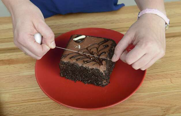 Dental floss is used as a cake cutter Wednesday, Aug. 20, 2014, at the Times Union in Colonie, N.Y. (Will Waldron/Times Union) Photo: WW / 00028237A