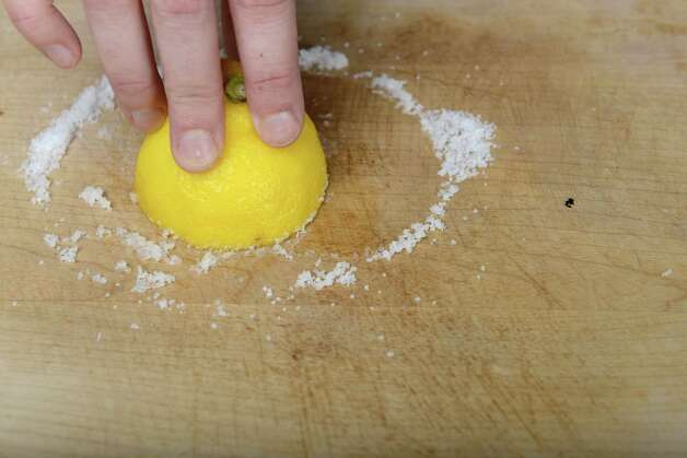 A salted lemon half is used to clean a cutting board Wednesday, Aug. 20, 2014, at the Times Union in Colonie, N.Y. (Will Waldron/Times Union) Photo: WW / 00028237A