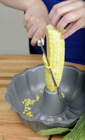 A bundt pan is used to hold corn and collect kernels while cutting Wednesday, Aug. 20, 2014, at the Times Union in Colonie, N.Y. (Will Waldron/Times Union) Photo: WW / 00028237A
