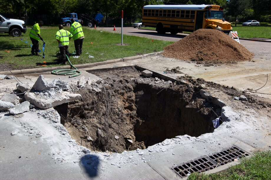 The City of Houston Public Works department repairs a 20-feet wide and 8-feet deep sink hole at the corner of Hilcroft Aveunue and Greenscraig Drive. The hole was caused by two busted storm pipes according to a Public Works employee. Photo: Gary Coronado / Houston Chronicle