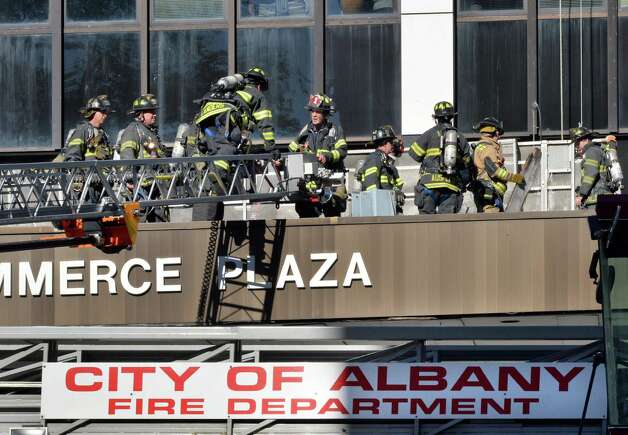 Albany firefighters climb onto One Commerce Plaza from Ladder No. 1  Friday Oct. 3, 2014, in Albany, NY.  (John Carl D'Annibale / Times Union) Photo: John Carl D'Annibale / 00028872A
