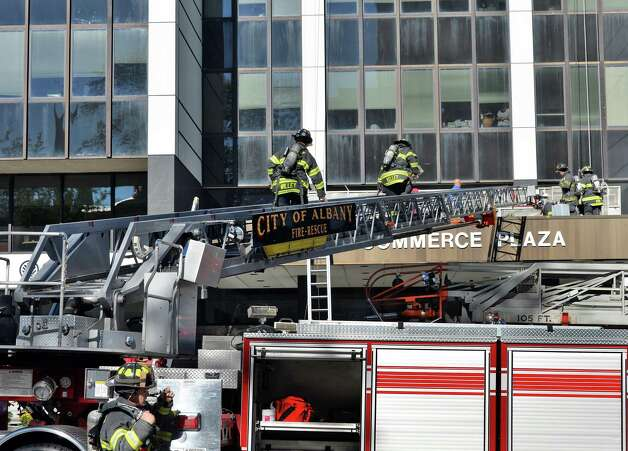 Albany firefighters climb onto One Commerce Plaza from Ladder No. 1  during a fire call Friday Oct. 3, 2014, in Albany, NY.  (John Carl D'Annibale / Times Union) Photo: John Carl D'Annibale / 00028872A