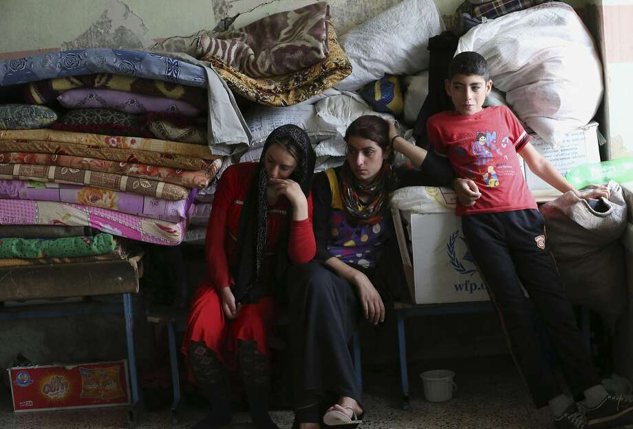 Internally displaced Iraqi Yazidis who fled from Sinjar and other towns after advances by Islamic militants take shelter at a school in Dahuk, 260 miles (420 kilometers) northwest of Baghdad, Thursday, Oct. 2, 2014. The Yazidis now living in the Kurdish city of Dahuk are cautiously optimistic - wary after having already lost so much, but hopeful to return home and pick up the pieces, as the Kurdish military says it is now on a push toward Sinjar, located in the deserts of northwestern Iraq near the Syrian border, in an assault aimed at retaking the town from the extremists. (AP Photo/Hadi Mizban) Photo: Hadi Mizban, Associated Press