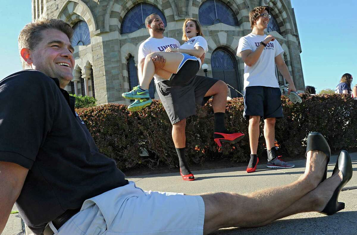 From left, swimming and diving team coach Scott Felix smiles as members of his team Jeremy Sagaille, Patricia Maragus and Matt Hellaver have fun before the Walk A Mile In Her Shoes event at Union College on Friday, Oct. 3, 2014 in Schenectady, N.Y. The The event was to raise awareness for sexual assault. (Lori Van Buren / Times Union)