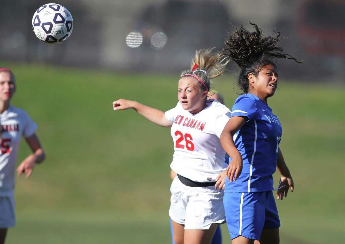 New Canaan's Courtney Overacker and Darien's Kendra Fitzpatrick go up for a header in FCIAC soccer action on Monday Sept. 30, 2013.