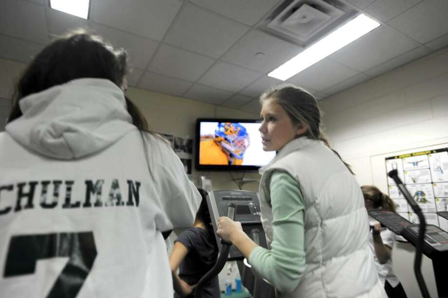 Pam Schulman, a freshman left, and Eliza Hompe, a senior, both Greenwich Academy varsity hockey players, watch the USA Women's Team semi-final game at the Olympics, while working out at Greenwich Academy, on Monday, February 22, 2010. Photo: Helen Neafsey / Greenwich Time