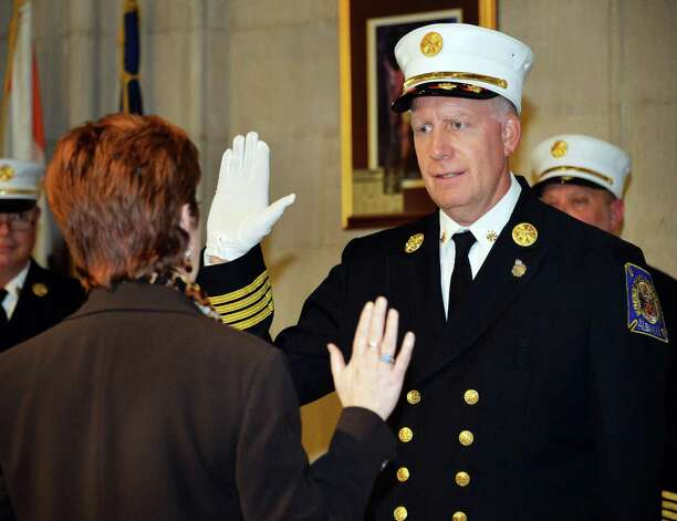 Mayor Kathy Sheehan, left, swears in new Executive Deputy Chief of the Department of Fire & Emergency Services Joseph J. Toomey during a promotion ceremony Friday Oct. 3, 2014, in Albany, NY.  (John Carl D'Annibale / Times Union) Photo: John Carl D'Annibale / 00028872A