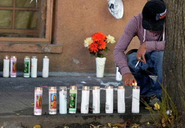 Friends of the shooting victim set up a memorial in front of 352 First St. where blood stains were washed from the sidewalk and memorial candles were put in its place Friday afternoon Oct. 3, 2014 in Albany, N.Y.  An unidentified man lights a memorial candle for the deceased man, Jorge Falu-Garcia.  (Skip Dickstein/Times Union) Photo: SKIP DICKSTEIN