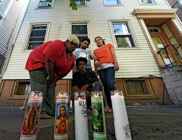 Friends of the shooting victim, Jorge Falu-Garcia, set up a memorial in front of 352 First St. where blood stains were washed from the sidewalk and memorial candles were put in its place Friday afternoon Oct. 3, 2014 in Albany, N.Y.  The friends are; left to right, Domanek Harrison, Felix Ilert, foreground, Noah Maisonet, background and Breanna Maisonet, right.    (Skip Dickstein/Times Union) Photo: SKIP DICKSTEIN