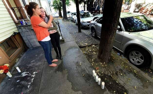 Breanna Maisonet, left, comforts a friend in front of 352 First St. where blood stains were washed from the sidewalk and memorial candles were put in it's place Friday afternoon Oct. 3, 2014 in Albany, N.Y.  (Skip Dickstein/Times Union) Photo: SKIP DICKSTEIN