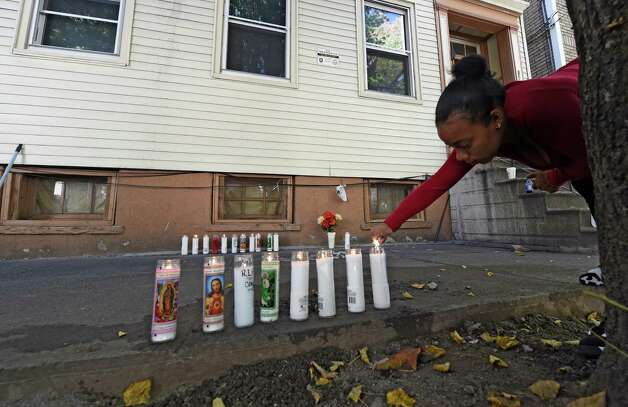 Friends of the shooting victim set up a memorial in front of 352 First St. where blood stains were washed from the sidewalk and memorial candles were put in its place Friday afternoon Oct. 3, 2014 in Albany, N.Y.  Destiny Gonzalez lights a memorial candle for the deceased man, Jorge Falu-Garcia. (Skip Dickstein/Times Union) Photo: SKIP DICKSTEIN