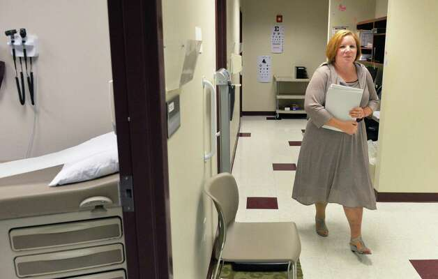 Office manager Stacy Smith works past examination rooms at Ellis Medicine's newest primary care practice and blood draw lab on Route 9 Friday Oct. 3, 2014, in Malta, NY.  (John Carl D'Annibale / Times Union) Photo: John Carl D'Annibale / 00028879A